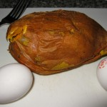 The cooked sweet potato beside two large eggs.